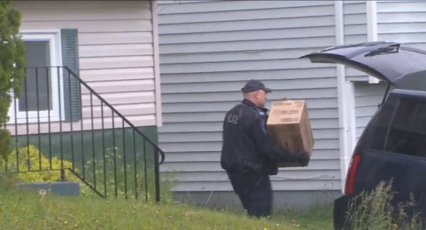 A police officer removes boxes from Alice Drive