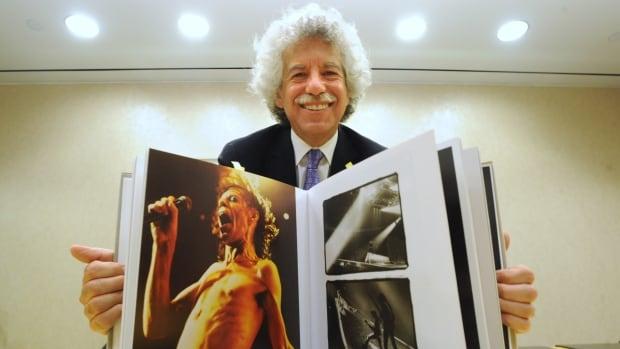 Harley Mintz poses with a book of Annie Leibovitz photos. His family bought the collection of 2,000 prints from the photographer and donated it to the Art Gallery of Nova Scotia.