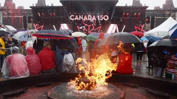 People take shelter from the rain on Parliament Hill as the Centennial Flame burns on July 1, 2017. The popular monument is being rebuilt to include Nunavut's symbols.