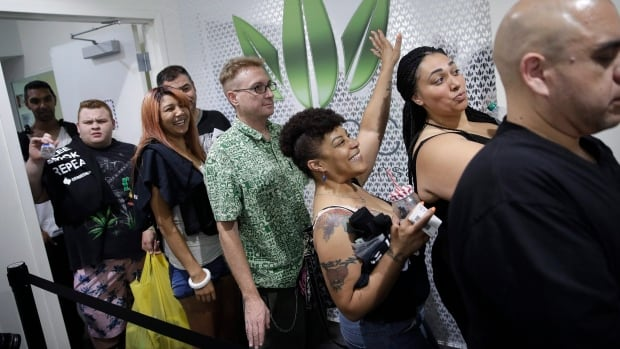 People wait in line at the Essence cannabis dispensary on Saturday.