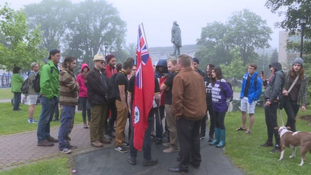 Chief Grizzly Mamma's protest was nearly disrupted when a group of men wearing black and yellow polo shirts showed up carrying the Red Ensign flag.