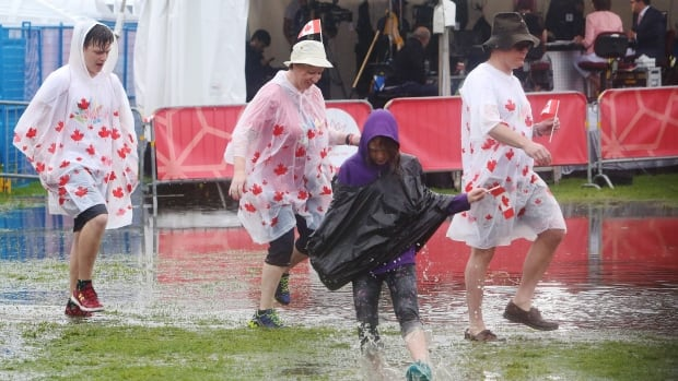 People walk through puddles on Parliament Hill as they take in the Canada 150 celebrations on a rainy Saturday.