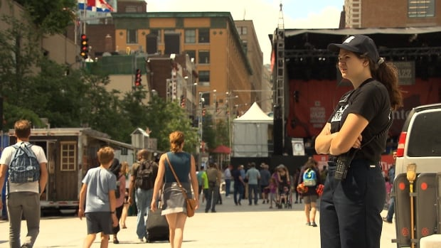 A security guard watches as people walk around the Place des Arts for the Montreal International Jazz Festival.