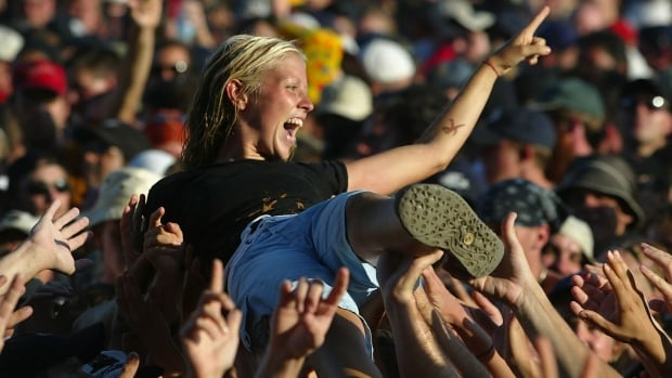 TORONTO, CANADA - JULY 30:  Buoyed up by fellow concertgoers, a fan crowd surfs during the SARS relief concert held at Downsview Park July 30, 2003 in Toronto, Canada. An estimated 490,000 fans showed up for the daylong music festival headed by the Rolling Stones.  (Photo by Donald Weber/Getty Images)