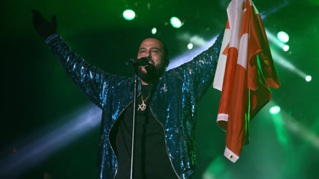 The Canadian rapper Belly raises a Canadian flag during last night's performance at Nathan Phillips Square. His performance caused a stir of complaints as many people were unhappy with his use of profanity.