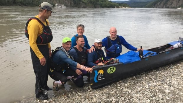 Team 57, Yukon Wide Adventures, brought together six paddlers with experience as solo racers. The strategy paid off: here team members pose in Dawson City with some celebratory Champagne.