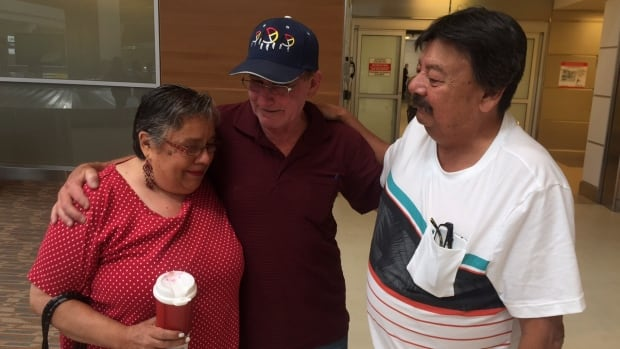Siblings Penny Carberry, Brent Mitchell and Ron Mitchell embrace just minutes after meeting for the first time after all being adopted out during the Sixties Scoop.