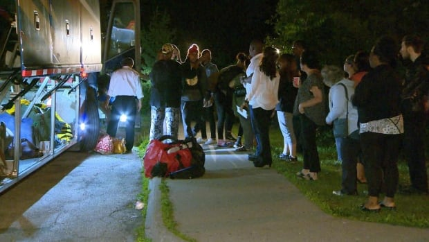 Students from C.W. Jefferys Collegiate Institute arrive home from Algonquin Provincial Park overnight Thursday. Their classmate, Jeremiah Perry, went missing on Tuesday while swimming.