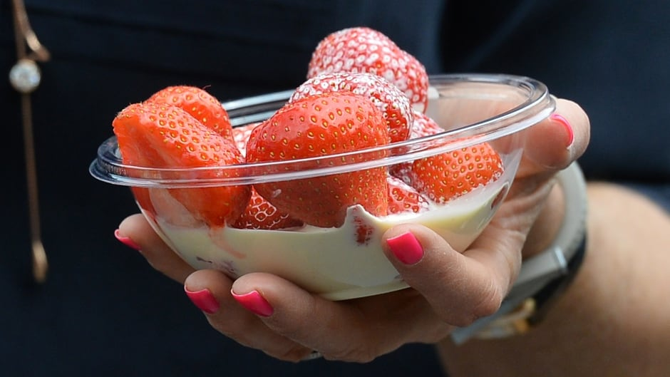 A spectator carries strawberries and cream on day three of the 2013 Wimbledon Championships tennis tournament at the All England Club in Wimbledon, southwest London.