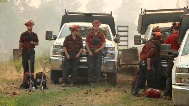 Firefighters take a breather while battling an out-of-control wildfire near Princeton, B.C.