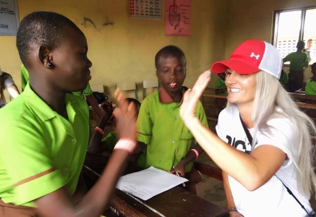 Kaylyn Kyle high-fiving student in Ghana