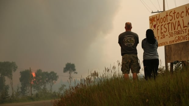 A couple watch the forest burning in the distance from Highway 97 north of 100 Mile House.