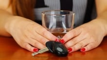 Impaired driver woman with drink keys drunk driving