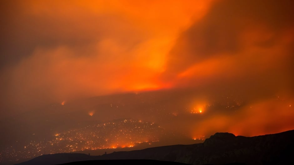 A wildfire burns on a mountain in the distance east of Cache Creek, B.C., in the early-morning hours of July 10, 2017.