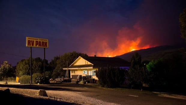 A wildfire burns on a mountain behind an RV park office in Cache Creek, B.C., in the early morning hours on July 8, 2017. (Darryl Dyck/Canadian Press)