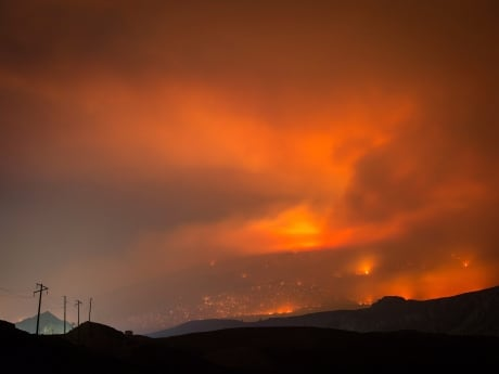 Aggressive wildfires have burned more than 236 square kilometres of B.C. so far this year. Here, a wildfire burns on a mountain in the distance east of Cache Creek on July 10. (Darryl Dyck/Canadian Press)