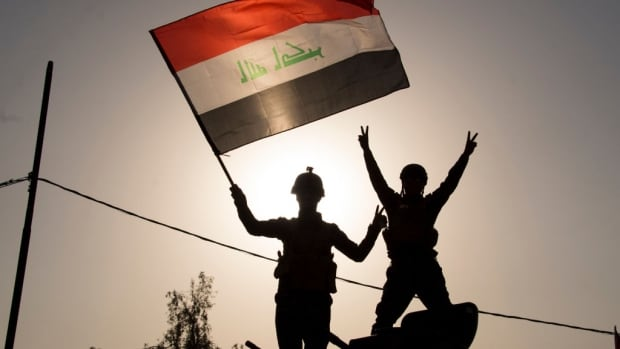 "Iraq's federal police members wave Iraq's national flag as they celebrate in the Old City of Mosul on July 9, 2017 after the government's announcement of the ""liberation"" of the embattled city."