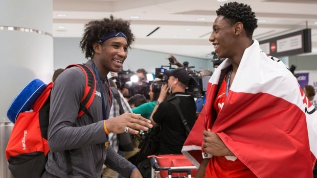 R.J. Barrett, right, and Abu Kigab arrive at Toronto's Pearson Airport Monday with other members of Canada's under-19 basketball team after winning gold at the U19 FIBA World Cup on the weekend.
