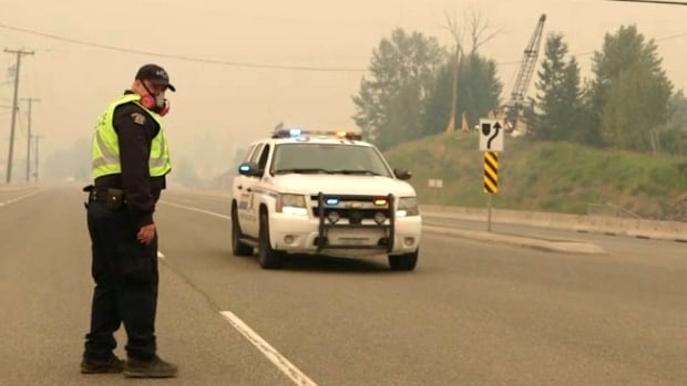 As smoke fills the skies, an RCMP officer stands on the road in the Williams Lake area. The entire city was placed under an evacuation alert late Monday.
