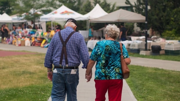 Wildfire evacuees McLean Rislund, 80, and June Rislund, 81, from Forest Grove near 100 Mile House, walk to an evacuation registration centre in Kamloops, B.C. on Monday. So far, more than 14,000 people have been affected by evacuations province-wide due to fire.