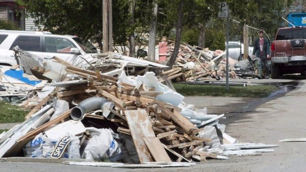 Flood debris piles up on a street last month in Laval, Que. The Quebec government announced Tuesday it is ramping up efforts to inspect damaged homes.