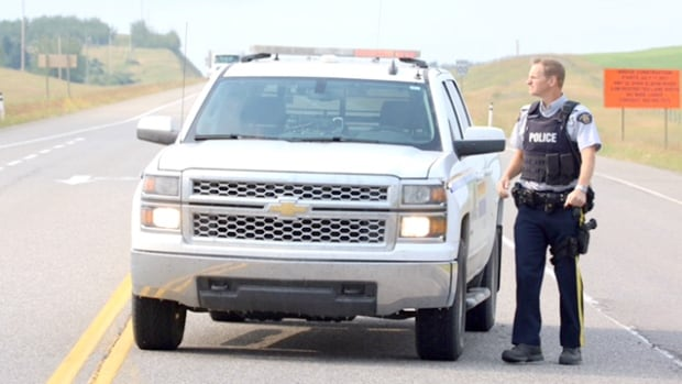 An RCMP officer stops traffic west of Calgary where a body was found Wednesday.
