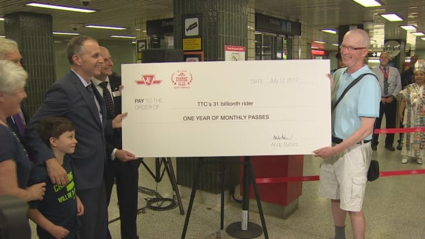 Long-time rider James White, right, seen here with TTC Chair Josh Colle and CEO Andy Byford, was randomly selected to represent TTC's 31 billionth customer.