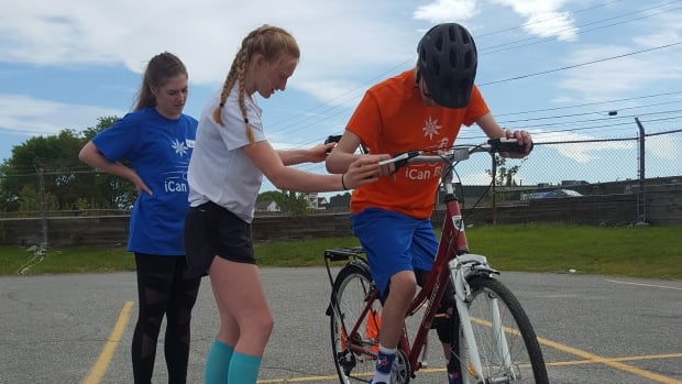 iCan Shine bike program volunteers help a participant learn how to bike during a program held in Sudbury in July of 2017.