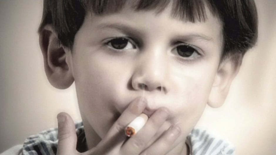 "In this screen capture from Maria Marshall's film ""When I Grow Up I Want To Be A Cooker,"" a young child is seen smoking."