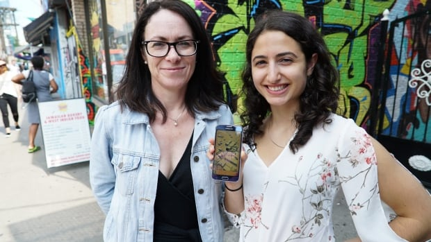 Professor Siobhan O'Flynn (left) stands with one of her students, Natalie Simonian, to show off the 'Toronto Kensington Market Hidden Histories' app that was created through a class project at U of T.
