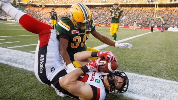 Greg Ellingson of the Redblacks reaches for a touchdown but falls short as Arjen Colquhoun of the Eskimos gives chase to help Edmonton defeat Ottawa 23-21 on Friday, in Edmonton, Alta.