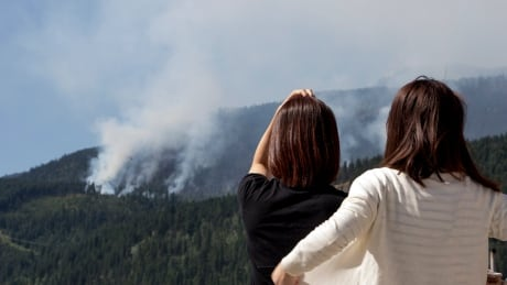 BC Wildfire People stop at gas station to watch mountain burn