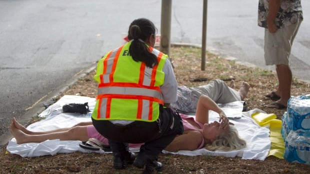 A paramedic checks on a woman, lying on a median, after she and others exited the Marco Polo apartment complex while firefighters continued to battle a blaze at the highrise Friday in Honolulu.