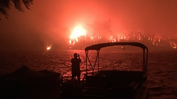 Shawn Cahill watches as a wildfire approaches his cabin on the other side of Loon Lake on July 15, 2017.