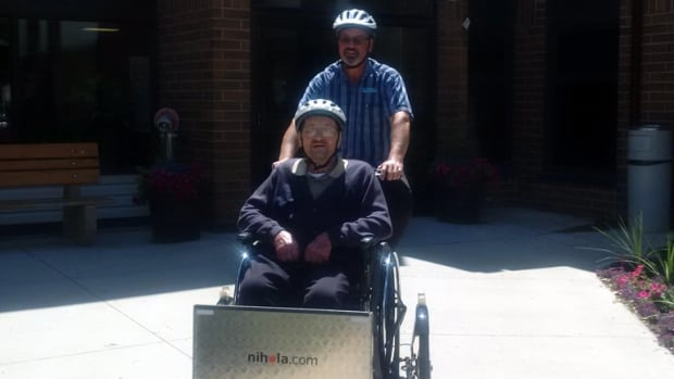 Dave Thiessen of Rest Haven Nursing Home takes a resident for a spin in the home's custom-built wheelchair-accessible bicycle.