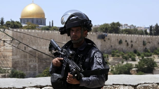 An Israeli border police officer stands guard outside in Jerusalem's Old City Friday, after three assailants opened fire on Israeli police from inside a major Jerusalem holy site, killing two officers before being shot dead, police said. The holy site reopened Sunday.