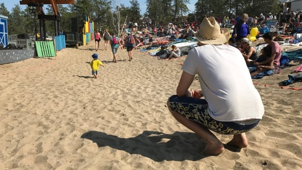 A dad keeps a close eye on his son walking on the sand at the main stage in the early afternoon sun.