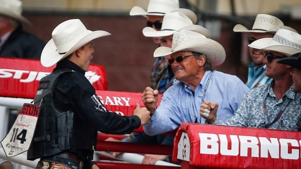 Zeke Thurston, left, of Big Vlley, Alta., celebrates winning the saddle bronc rodeo finals for the third year in a row at the Calgary Stampede.