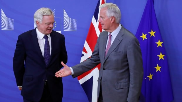 U.K. Secretary of State for Exiting the European Union David Davis, left, is welcomed by the European Commission's chief Brexit negotiator Michel Barnier at the start of a first full round of talks on Britain's divorce terms from the European Union, in Brussels, on Monday.