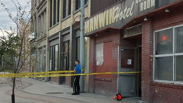 A police cadet guards the scene in front of the Manwin Hotel on Monday morning.