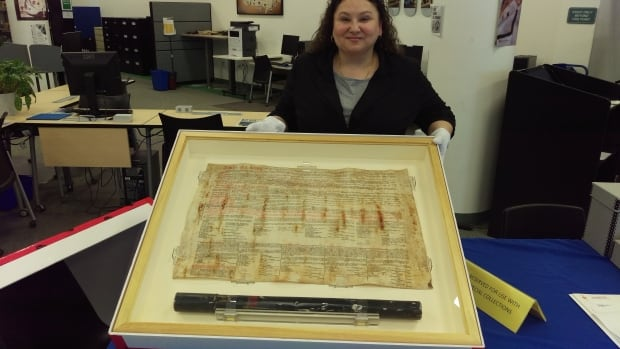 Paula Daigle, librarian for the First Nations University of Canada, holds up the glass case that houses the 1899 original travelling copy of Treaty 8.