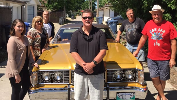 Family stands with vintage car