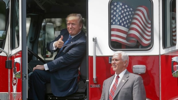 Trump, accompanied by Vice-President Mike Pence, gives a 'thumbs-up' from inside the cabin of a firetruck during a 'Made in America,' product showcase Monday on the South Lawn of the White House in Washington. (Martinez Monsivais/Associated Press)