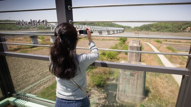 A South Korean woman takes a picture from a Demilitarized Zone observation post at Majeong-Ro, South Korea. Long-time adversary North Korea is in the distance. A meeting between the two is proposed for July 21.