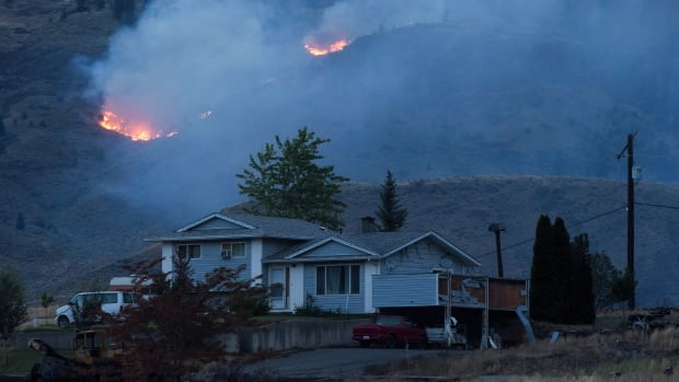 A wildfire burns on a mountain in the distance behind a house that remains standing on the Ashcroft First Nation, near Ashcroft, B.C., late Sunday, July 9, 2017.