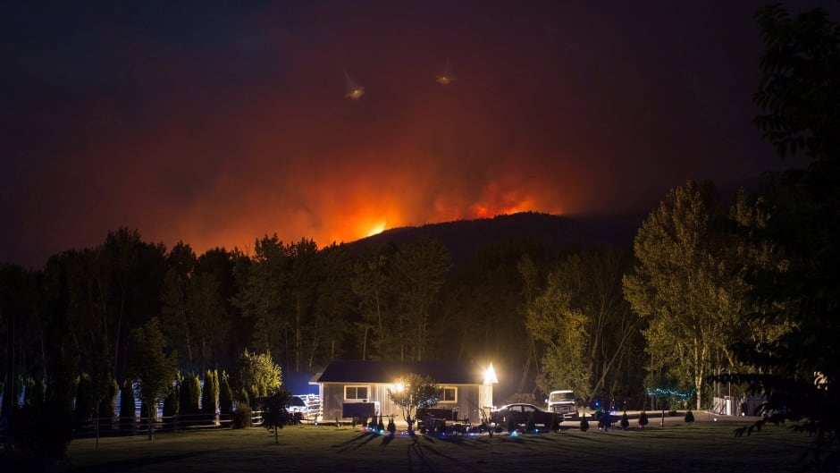 A wildfire burns on a mountain behind a home in Cache Creek, B.C., in the early morning hours of Saturday July 8, 2017.