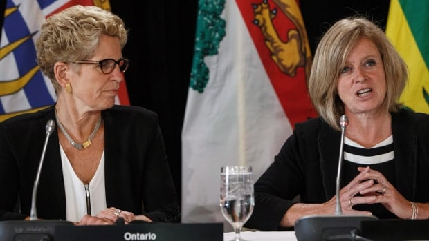 Ontario Premier Kathleen Wynne, left, looks to Alberta Premier Rachel Notley as she speaks during the final press conference at the Council of Federation meetings in Edmonton. Premiers discussed pot delays, court delays and the opioid crisis.