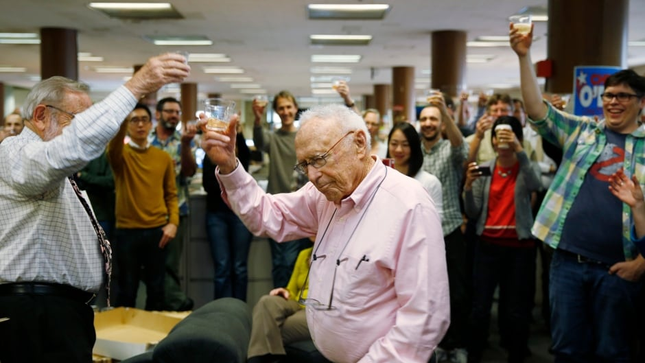 David Perlman, centre, helps lead the newsroom at the San Francisco Chronicle in a toast as the paper celebrated 150 years of operation on Jan. 16, 2015. Perlman is now retiring from the paper after 77 years.
