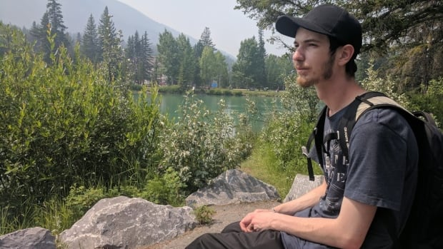 Josh Smith pretends to sightsee in Banff in order to avoid looking like he's loitering in the park. Smith has a job in the mountain town, but hasn't been able to find affordable housing.