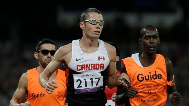 Canada's Jason Dunkerley, seen in this file photo running beside guide Josh Karanja at the 2012 Paralympics, won a silver medal in the T11 1,500 metres Friday at the world para athletics championships in London.